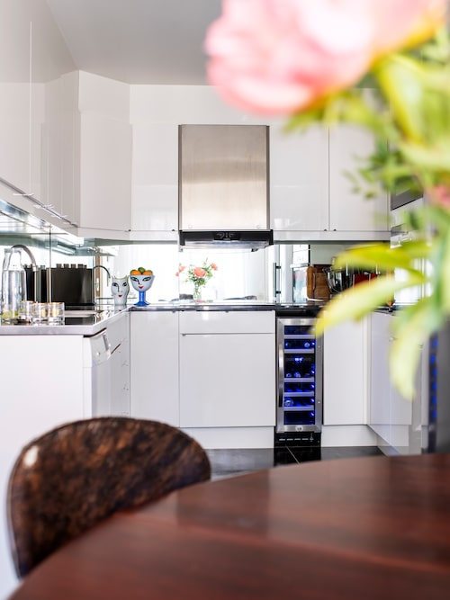 """I köket står vaser från Ulrica Hydman-Vallien, 80-talsklassiker med de ikoniska motiven Open minds och Face. Här finns även en liten vinkyl. """"Jag är glad i goda viner, vilket kan komma från tiden vi bodde i Australien. Det är alltid trevligt att ta ett glas vin ute på terrassen när det är varmt!"""""""