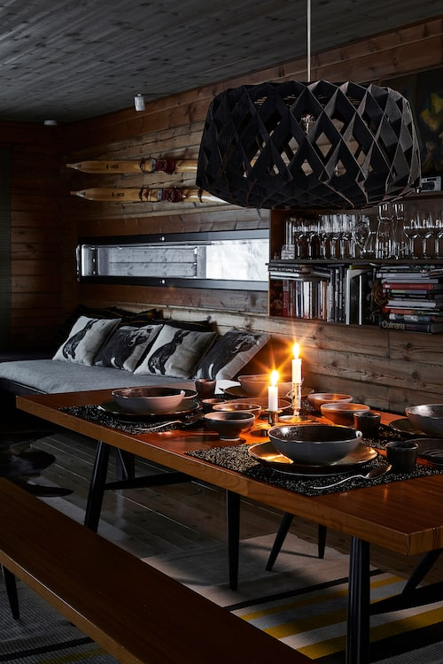 Träskidorna på väggen och kuddarna med djurmotiv i de väggfasta sängarna förstärker vildmarkskänslan. Taklampan i massiv björk heter Pilke och kommer från Showroom Finland.