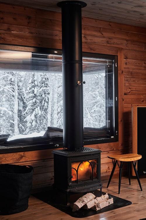 Kaminen från norska Jetul sprider värme och skyhög mysfaktor från sin centrala plats. Pirkkapallen matchar interiören perfekt och är en favorit hos Antti.