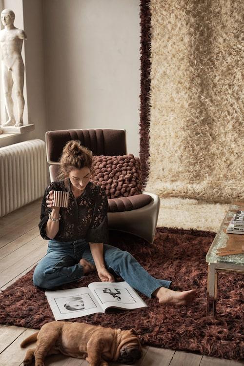 Marie Olsson Nylander med hunden Bullen på en av mattorna hon designat för Ellos Home. Mer info och köp här (klicka på bilden för länk till Ellos).