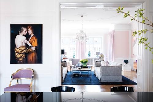 """Bilden på de två kvinnorna är ett verk av konstfotografen Julia Hetta. Vardagsrummets väggar har fått en matt rosa nyans från Zoffany. """"Vi har främst rosa och blått i våningen. Färgerna skiftar beroende på hur ljuset faller, just vardagsrummet känns väldigt krispigt när solen ligger på,"""" säger Maria. I vardagsrummet hänger en vintage Baccaratkrona i kristall. """"Ett passande smycke för det här rummet som har avbildande änglar i stuckaturen"""". Soffgrupp från Oscar&Clothilde, matta från Kasthall."""