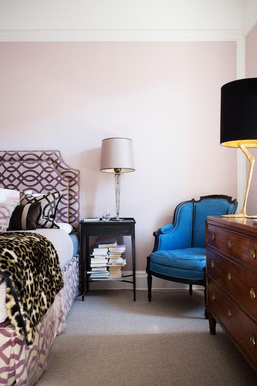 Sovrummet med stoppad sänggavel, kuddar och heltäckningsmatta har en ombonad hotellkänsla. Bordslampa från Oscar&Clothilde.