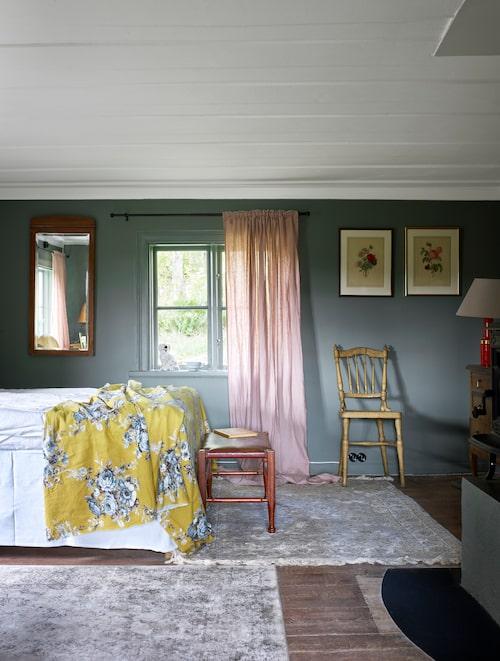 Vilsamt gröna väggar matchas av blekrosa gardiner i ett av sovrummen på övervåningen.