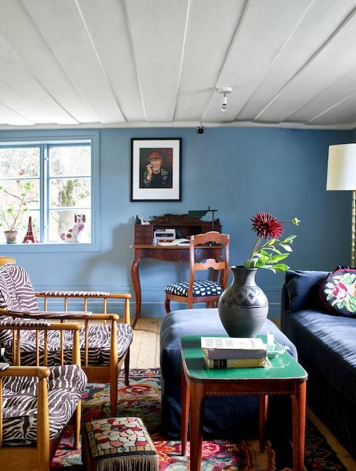 Sittgrupp i salen. Fåtöljerna, med zebramönstrat tyg, är Skrindan av Kerstin Heurlin-Holmquist. På väggen hänger ett självporträtt av Plura.