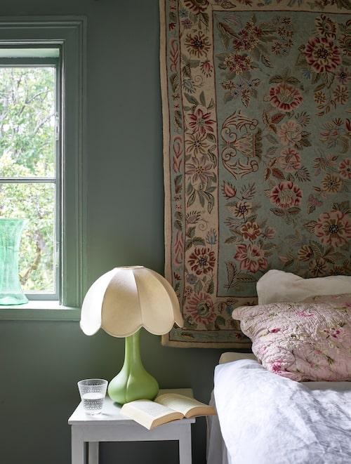 Den blommiga mattan som nu hänger på väggen fanns i huset. Den lilla gröna sänglampan med vit skärm är ett fynd från traktens bästa loppis.