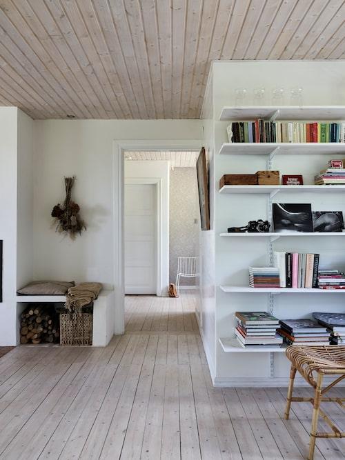 En av väggarna i vardagsrummet är inklädd med hyllplan där allt från gamla fotografier till trädgårdsböcker samsas.