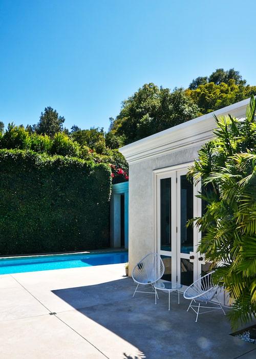 """Här är poolen en smal remsa, och det är poolhuset med dess terrass gjord av väl tilltagna betongplattor som står i centrum. Därinne kan det mesta rymmas – bastu, lounge, möbelförvaring. Stilen är klassisk, med husets krön som går igen i pelarna. De 50-talsinspirerade möblerna kontrasterar. Här tar man gärna en kvällsdrink med sin """"poolare""""."""
