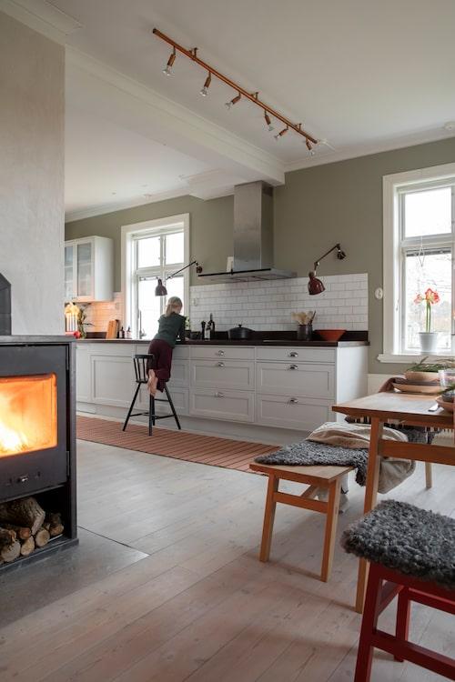 Till advent plockar Emelie fram fårskinnen som är köpta på en gård i närheten. Den fina bänkbelysningen i köket, industrilampan PJ72, kommer från Örsjö, precis som takskenan Star. Kaminen från Wiking värmer skönt under kalla vinterdagar.