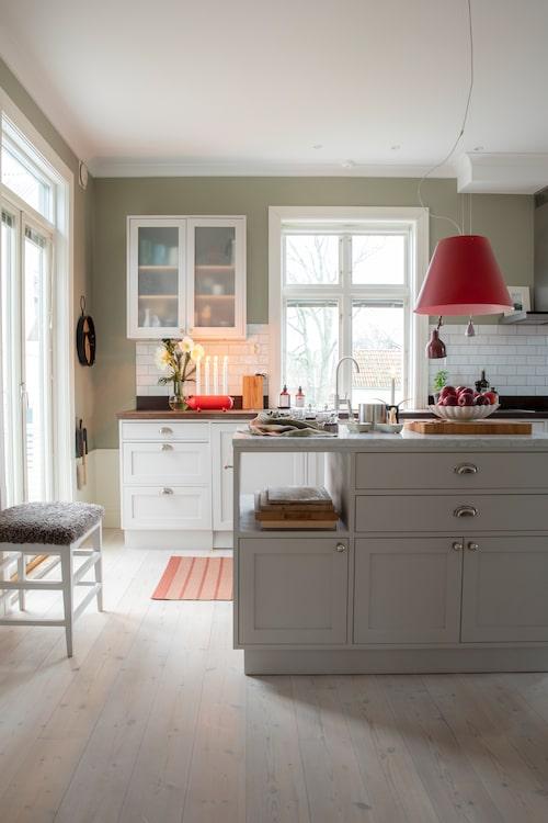 Nu har familjen massor av idéer för den stora trädgården att förverkliga men först väntar adventstid med kakbak i det trivsamma köket. Köksmodulerna är målade i den varmvita nyansen Cornforth white från Farrow and Ball,  den röda lampan, Costanza från Luceplan, är Kristians favorit.