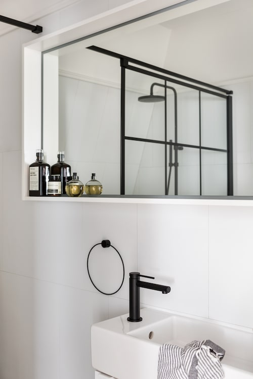 Duschen bakom glasvägg följer upp stilen från köket. Takdusch från Duschbyggarna, tvättställ från Ikea med blandare, Miller.