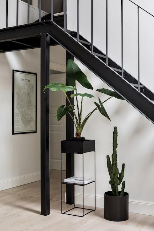 Blomsterpiedestalen i svart metall, från Svenska hem, följer upp trappans industriella uttryck.