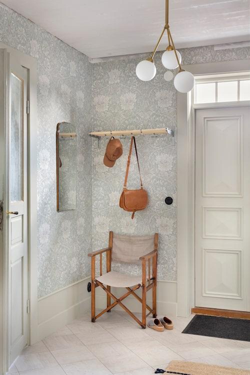 Sebastian har snickrat de höga golvsocklarna i hallen och även klätt om stolen som är köpt på Vadstena Antik. Molly har byggt om hatthyllan som är ett auktionsfynd. Taklampan är från Lampgallerian.