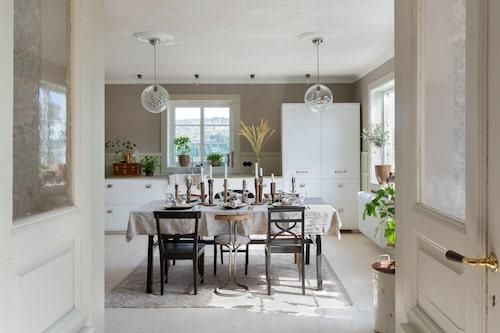 Ikea-köket har fått platsbyggd känsla med hjälp av täcksidor och lister runt och mellan stommarna. Den lilla köpmansdisken på bänken är en gåva. Lampor från Svenska Armaturer. De glasade pardörrarna hittades via radioprogrammet Sök och Finn i P4.