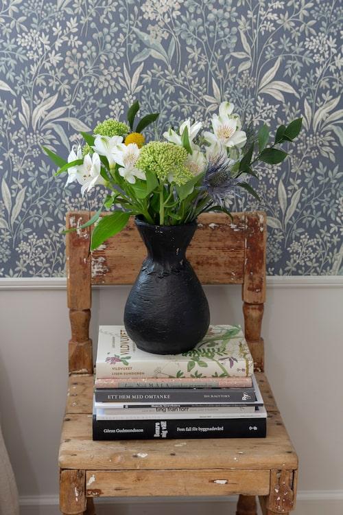 En gammal stol med vacker patina används som sängbord. Vasen är fyndad på loppis och ommålad av Molly.