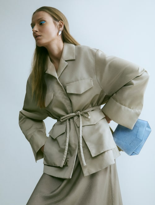 Jacka av nylon, 5 200 kr, Totême. Slipklänning av polyester, 199 kr, H&M. Örhängen av silver, 890 kr, Drakenberg Sjölin. Väska av skinn, 19 000 kr, Byredo.