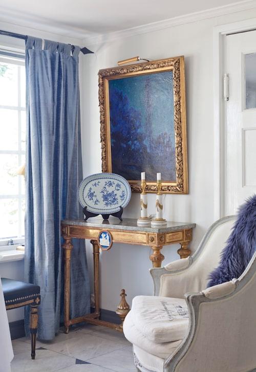En bergère, fåtölj i rokokostil från 1900-talet och ett sengustavianskt konsolbord skapar trivsel i den inre delen av hallen.