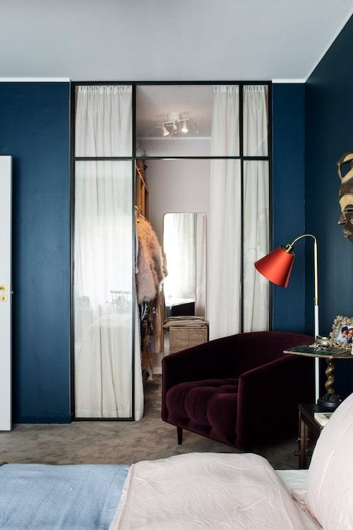 Den djupblå väggfärgen är Solitary blue ur serien Lycke från Happy homes. Glaspartiet in mot sovrummets walk-incloset kommer från Edlund smide. Fåtölj, Meli meli, röd lampa, Vallentuna armatur.