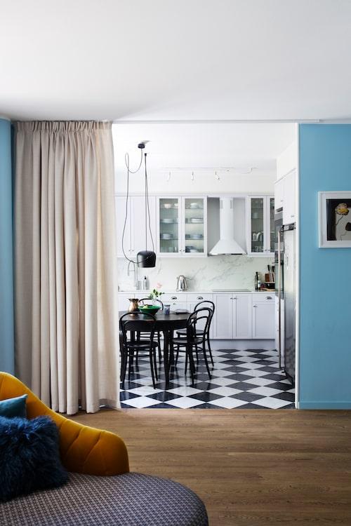 Charlotte Asplund från By Asplund projektledde renoveringen och kom med idén att köksinredningen skulle behållas men lackas om i samma grå färg som väggarna i hallen. Vardagsrummets trägolv möter fint stengolvet i köket. Dagbädden i förgrunden är Lazy daydreamer från Bold monkey.