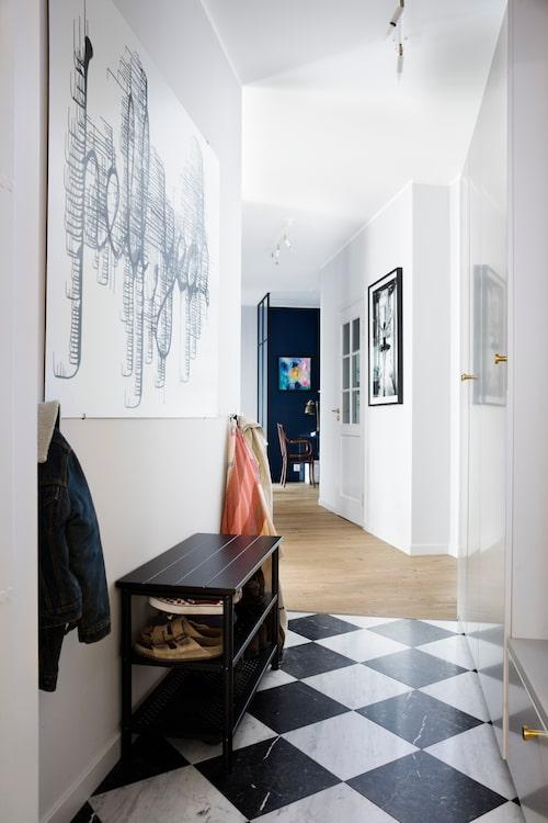 Den avlånga hallen binder ihop lägenheten med vardagsrum och kök till vänster, och sovrum och badrum till höger. Glasade spegeldörrar till alla rum får lägenheten att kännas öppnare och rymligare. Dörrar från Swedoor. I fonden skymtar arbetshörnan.