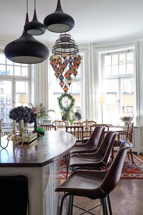 """Det stora köket har generösa sällskapsytor. Barstolar från Nordal, bord och stolar är antikfynd och den orientaliska takkronan är köpt i Turkiet. """"Både jag och Anders gillar att laga mat, men dukningen står jag för. Det är som en orgie av linnedukar, färska snittblommor och servettringar. Då får ingen störa – jag är besatt av att duka!"""""""