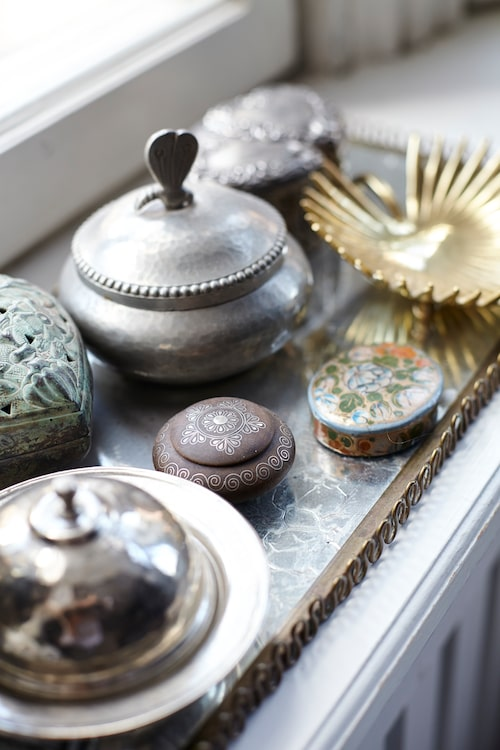 """Stilleben i sovrumsnischen med en auktionsfyndad bricka och små burkar som Dominika samlat på sig genom åren och kallar för """"Livets burkar""""."""