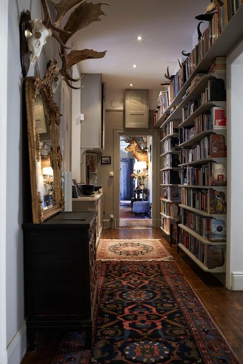 """I den långa hallen står böcker i en platsbyggd bokhylla. """"Anders läser snabbare än jag, cirka en bok om dagen medan jag snittar en bok i veckan. Han föredrar facklitteratur och jag skönlitteratur, men vi lurar båda på varandra favoriter från vår genre emellanåt."""""""