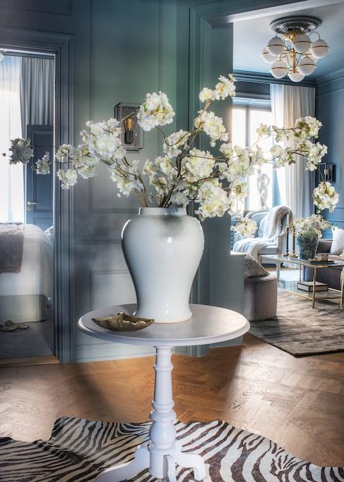 Hallens runda pelarbord är den perfekta platsen för ett välkomnande blomsterarrangemang. Härifrån har man fri sikt in mot sovrum, vardagsrum, badrum och kök – en unik planlösning som verkligen kommer till sin rätt om man betraktar varhe dörröppning som en tavla när man inreder. Tänk blickfång och något som lockar dig att kliva in. Pelarbord från Oscar&Clothilde, urna Newport, zebramönstrad matta, Zara home.