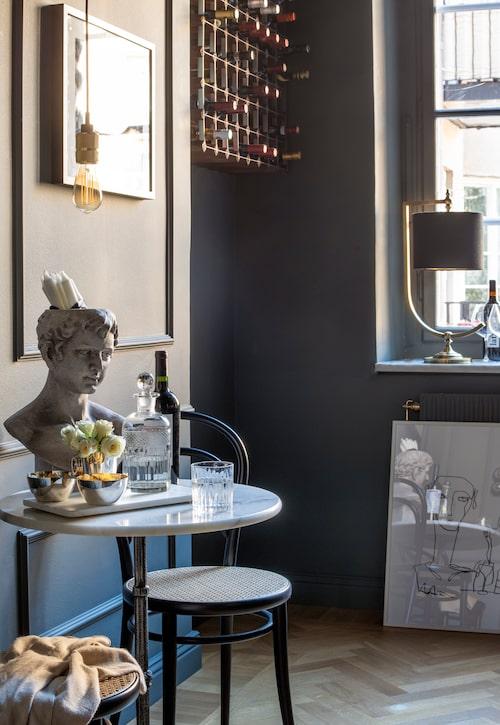 Lister, målade i samma grå kulör som väggarna, skapar liv i det monokroma. Kafébord från Trosa möbler, stol Ton no 14, Royal design, byst, silverskålar, karaff och lampan i fönstret, allt från Oscar & Clothilde. Taklampa Buster + Punch.