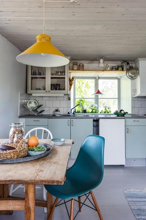 Köksluckorna fick ny färg när familjen flyttade in. Den gula taklampan följde med i köpet, och matbordet är byggt av Karins mormors far. Loppisfyndade stolar. Bricka från Maria Form i Visby.