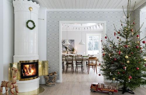 Sekelskiftesstilen klär det vackra nybyggda huset där kakelugnen sprakar och granen pyntas med klassiskt rött och guld. Bordet står dukat med linne, granris och juläpplen. Den tidstypiska 1800-talstapeten Liljesal är från Duro.