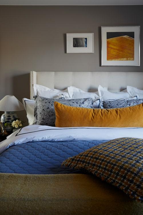 Sänggaveln har Tove själv designat och låtit tillverka i Spanien med tyg från Gaston y Daniela, sängkläder och överkast från Mille notti, den långa lejongula sammetskudden har Toves sömmerska sytt, pläden är vintage. Hundtandsmönstrad kudde och kinesiska Bojanlampor från Toves butik, tavlorna är köpta vintage.