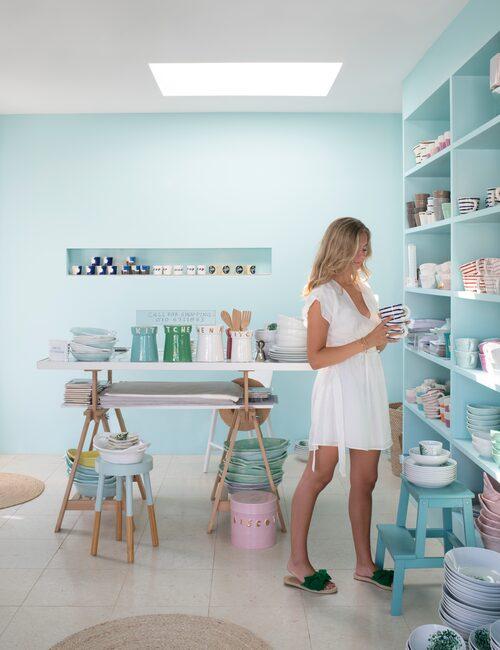 """Aqua-kulören på väggarna, Agnetas älsklingsfärg med doft av Medelhav, går igen i en hel del av keramiken. """"Flickan heter Clara, hon brukar hjälpa till i mitt showroom på sommaren."""""""
