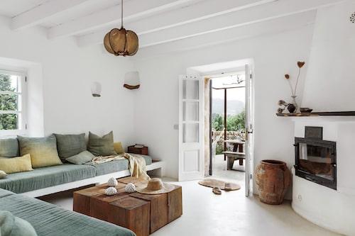 Mercedes älskar att stötta lokala hantverkare och konstnärer. Här i vardagsrummet har hon platsbyggt en soffa och de vackra överdragen och kuddfodralen är färgade och uppsydda hos företaget Espanyolet på Mallorca. Det charmiga bordet som består av nio trästockar är designade av Con alma, också från Mallorca. På bordet står vita keramikalster av Jaume Roig