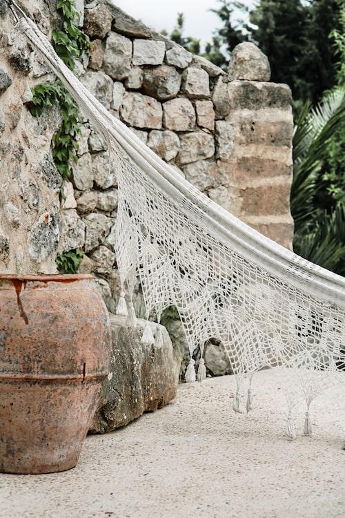 I ett hörn på gården har Mercedes hängt upp en hängmatta av klassiskt snitt, dit man kan dra sig undan för en tupplur.