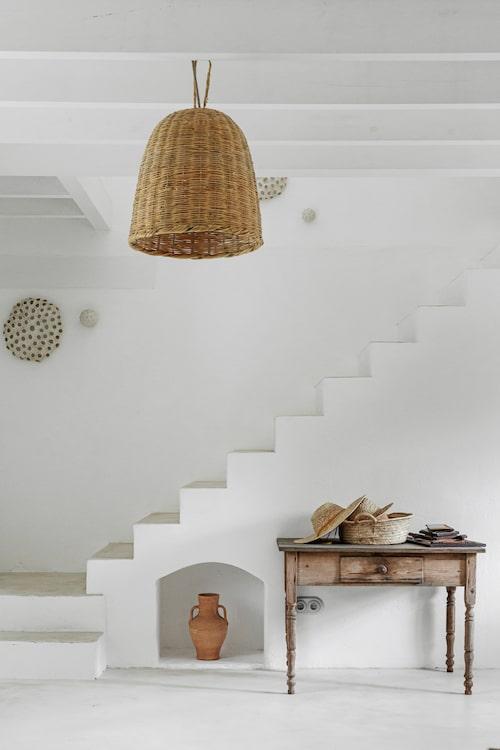 Vitt, vitt, vitt och några få möbler i trä och detaljer i naturmaterial. Ett vilsamt hem där tankarna får vandra fritt. På vintagebordet förvarar Mercedes sina solhattar. Lerkruset är typiskt på Mallorca. På väggen hänger konstverk av keramikern och vännen Jaume Roig.