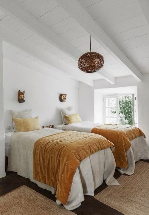 Sängarna i pojkarnas rum har överkast i vintagelinne och kuddar som är infärgade i gult. På sängarna ligger även varsitt överkast i orange plysch. Trädekorationerna över barnens sängar är bara några av alla charmiga, lokalt producerade hantverk i hemmet.