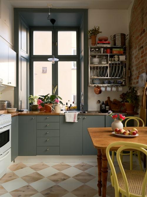 """""""Köket behövde verkligen sminkas upp lite"""", tyckte Nina. Det löste hon genom att måla golvet schackrutigt och sätta en grågrön nyans från Jotun Lady på skåp och fönsterkarm. Beslagen kommer från Byggfabriken. Metallhylla från Hay."""