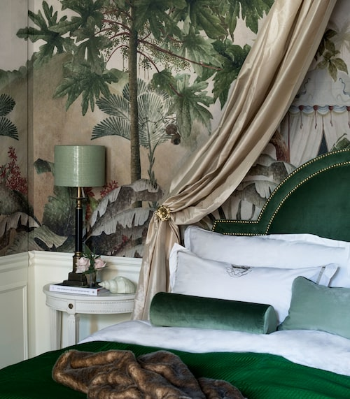 Sovrummets iögonfallande tapet från franska  Ananbô lämnar ingen oberörd. De gamla gardinerna syddes om till en sänghimmel, som välvts över sänggaveln klädd i djupgrön sammet från Mimosa by Inka. Lampor, Oscar&Clothilde, överkast, Mimou, pölkuddar, Mimosa by Inka, pälspläd, Newport.