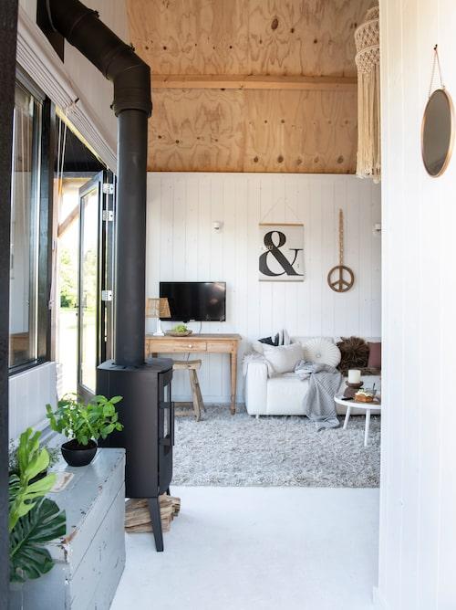 Den vita panelen går inte hela vägen upp till nock, för familjen ville skapa en fin kontrast med det nakna träet. Kaminen ger huset lite extra värme på vintern. Den blågrå trälådan bredvid är ett av många vintagefynd.