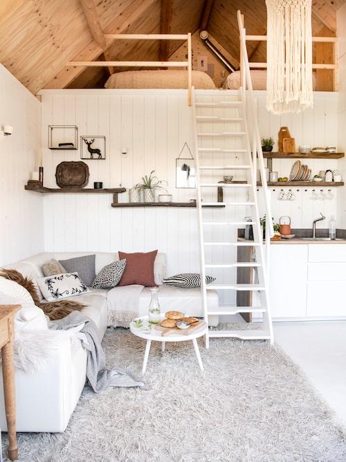 På 35 kvadratmeter ryms alla bekvämligheter: vardagsrum, kökshörna, badrum och sovloft. De rustika hyllorna ovanför soffan kommer från Frank Pouwer, som tillverkar inredning av återbrukat trä. Lampan som hänger ner från taket är gjord i makraméteknik och kommer från danska Skovbon.