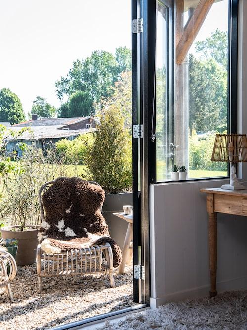 Genom de stora glasdörrarna når man husets egen uteplats. Rottingstolarna är vintagefynd, som så mycket annat i huset. Fårskinnen är bra att ha till hands, för det kan blåsa rejält här i det platta nederländska landskapet.