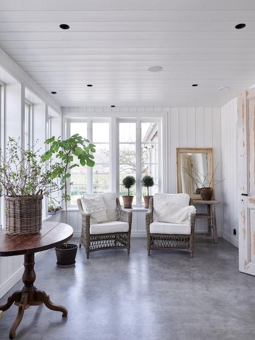 Entrén är byggd som en glasveranda, som gjord för både avskildhet och umgänge. Fönster från Nyebro Snickeri. Korgstolar, Artwood.