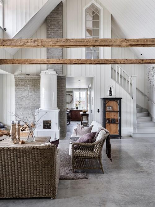 Allrummets takhöjd på hela 6,7 meter ger en sakral känsla som förstärks av det spetsiga fönstret i trappan. Den höga gamla kakelugnen har fått ett nytt liv på Perstorps gård.