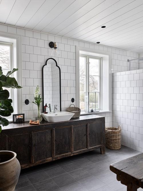 Klassiskt vitt kakel i halvförband ger badrummet en äldre karaktär som passar fint till det rustika badrumsskåpet. Skåp och urna från Room by Sarah. Tvättställ, Flod, Svedbergs. Lampa, PR Home.