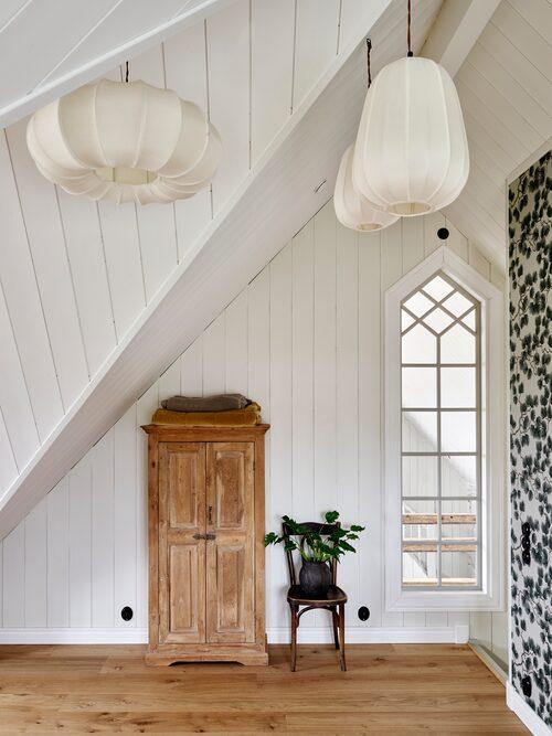 Uppe i sovrummet svävar tyglampor, från Snowdrops Copenhagen, som små moln under snedtaket. Tapet, Pine Green, Sandberg.