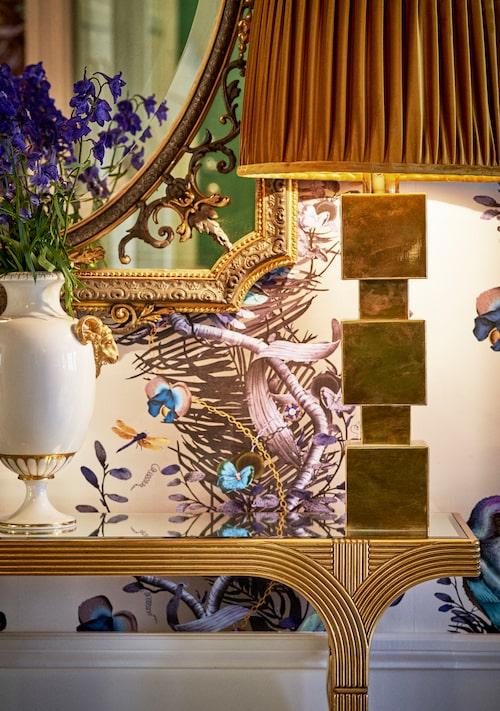 Hallbordet är belgisk art deco med spegelskiva som reflekterar ljuset från lampan och det metalliska taket. Italiensk lampfot, inropad på Bukowskis, med skärm från Hallbergs belysning. Även stilspegel och urna är inropade på auktion.