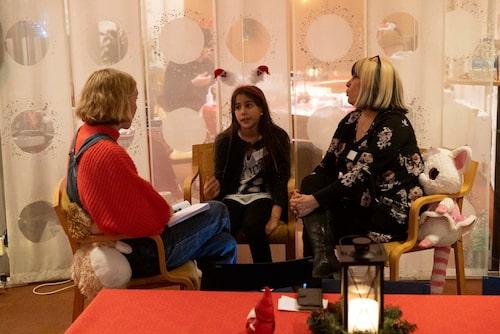Maja i ett samtal med två av volontärerna, Daniela och Nahid.