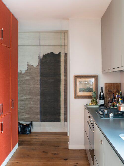 Väggen i köksdelen är målad i en ljusgrå färg från Farrow&Ball. Skåp och lådfronter är i mörkare grått. Kyl, frys och förvaring är inbyggda i skåpen till vänster.