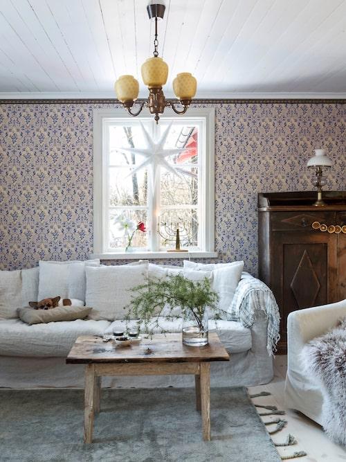 Tapeten i vardagsrummet är en reproduktion  av den gamla tapeten Nästgårds, bården heter Salsbården. En modern soffa och matta bryter av den äldre stilen.