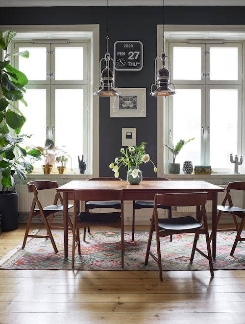 """""""Väggarna i vardagsrummet var mörkt blågrå när vi flyttade in och det blev fint när vi adderade våra saker."""" Taklamporna är gamla båtlampor. Matbord från antikaffär, stolar, Blocket."""